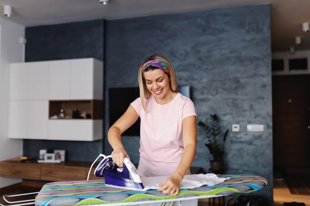 Attraktive lächelnde blonde hausfrau, die im wohnzimmer steht und kleidung bügelt.