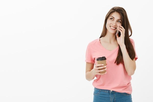 Attraktive lächelnde brünette frau, die im studio mit ihrem telefon und kaffee aufwirft