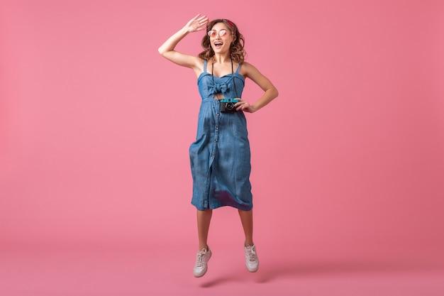 Attraktive lächelnde frau, die aktiv springt und foto auf weinlesekamera trägt, die denimkleid lokalisiert auf rosa hintergrund trägt