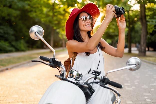 Attraktive lächelnde frau, die auf motorrad in der straße im sommerart-outfit reitet, das weißes kleid und roten hut trägt, der im urlaub reist und fotos auf vintage-fotokamera macht