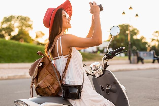 Attraktive lächelnde frau, die auf motorrad in der straße im sommerart-outfit reitet, das weißes kleid und roten hut trägt, der mit rucksack im urlaub reist und fotos auf vintage-fotokamera macht