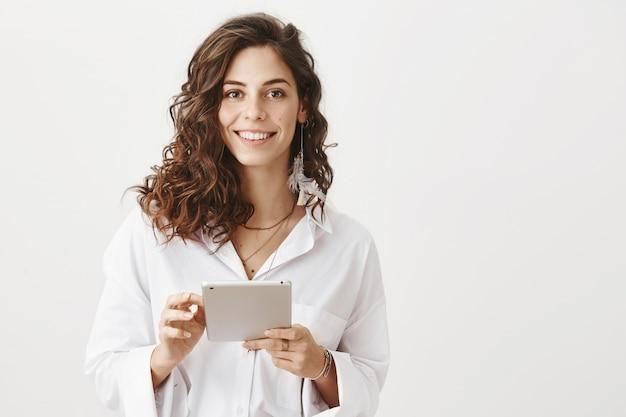 Attraktive lächelnde frau, die digitales tablett verwendet