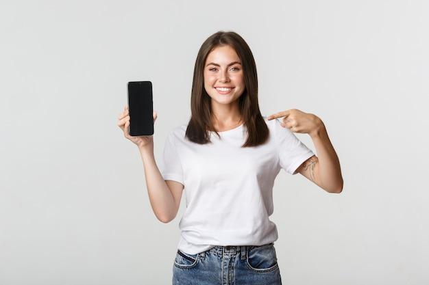 Attraktive lächelnde frau, die finger auf smartphonebildschirm zeigt, weiß.