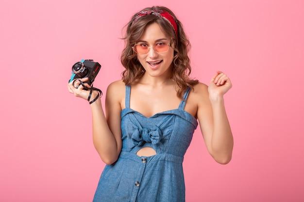 Attraktive lächelnde frau, die foto auf weinlesekamera nimmt, finger nach oben zeigend, jeanskleid und sonnenbrille lokalisiert auf rosa hintergrund trägt