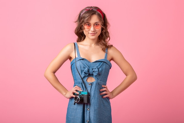 Attraktive lächelnde frau, die foto auf weinlesekamera trägt, die jeanskleid und sonnenbrille trägt, lokalisiert auf rosa hintergrund