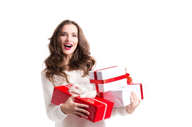 Attraktive lächelnde frau, die geschenke lokalisiert hält