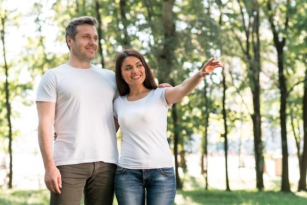 Attraktive lächelnde frau, die ihrem ehemann etwas bei der stellung im park zeigt