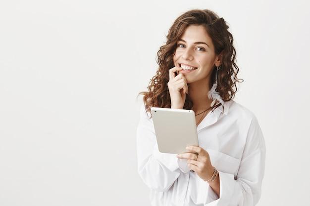 Attraktive lächelnde frau, die online mit digitalem tablett einkauft