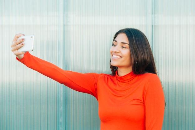Attraktive lächelnde frau, die selfie mit handy nimmt