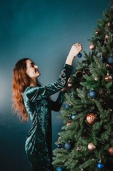 Attraktive lächelnde frau, die weihnachtsbaum verziert