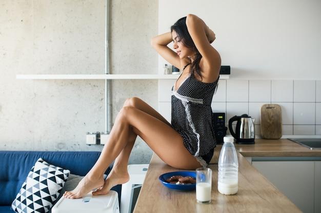 Attraktive lächelnde frau im pyjama, die in der küche am morgen lange dünne beine sitzt