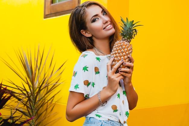 Attraktive lächelnde frau im urlaub in der gedruckten t-shirt-sommermode, hände, die ananas halten