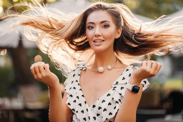 Attraktive lächelnde frau mit langen haaren, die spaß am sonnigen sommertag glücklich haben