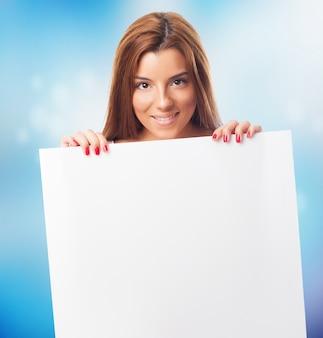 Attraktive lächelnde frau mit weißem zeichen