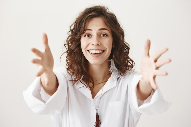 Attraktive lächelnde frau strecken hände aus, erreichen oder umarmen jemanden