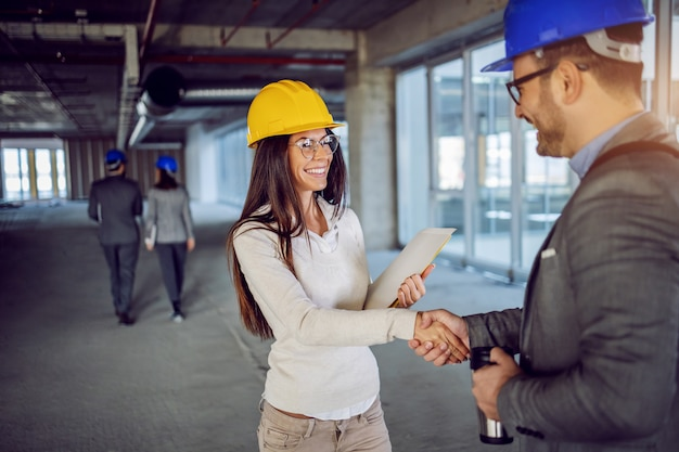 Attraktive lächelnde freundliche kaukasische architektin, die ihrem kollegen die hand schüttelt und ihm zu der großartigen idee für die erneuerung des gebäudes gratuliert.
