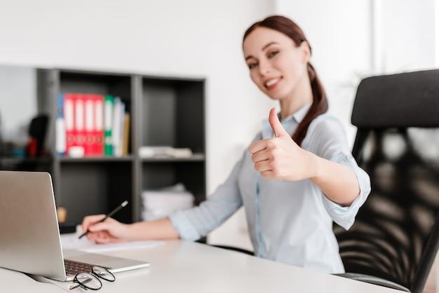 Attraktive lächelnde geschäftsfrau, die daumen herauf geste im fokus in den hellen büroräumen zeigt