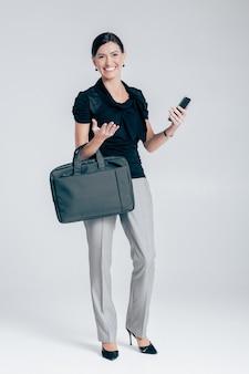 Attraktive lächelnde geschäftsfrau mit telefonhalterung auf grauem hintergrund