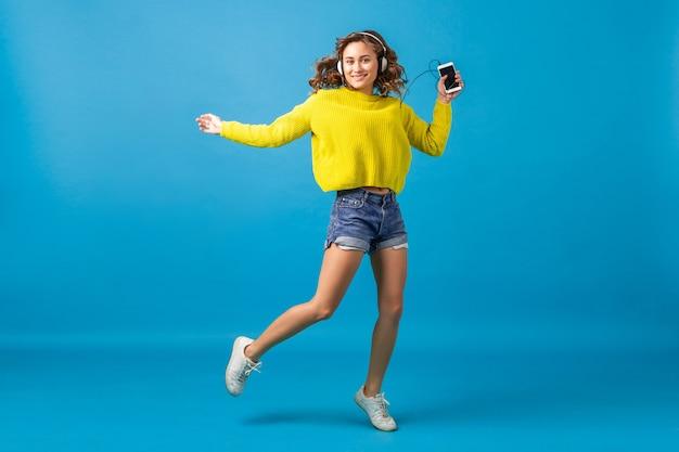 Attraktive lächelnde glückliche frau, die tanzt, hört musik in kopfhörern im hipster-outfit lokalisiert auf blauem studiohintergrund, trägt shorts und gelben pullover