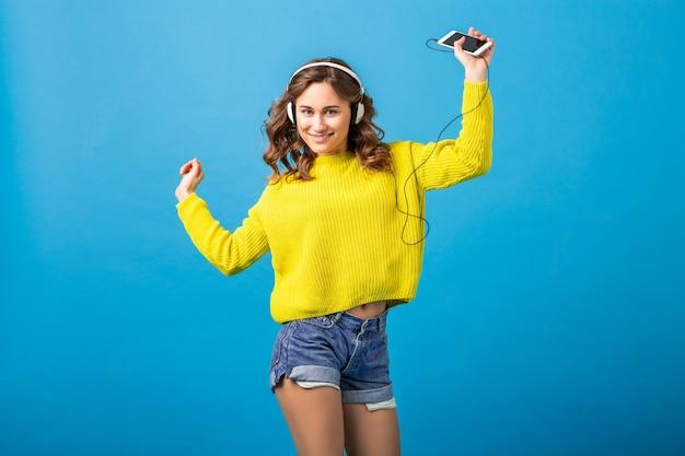 Attraktive lächelnde glückliche frau tanzt, die musik in den kopfhörern im stilvollen hipster-outfit lokalisiert auf blauem studiohintergrund hört, der shorts und gelben pullover trägt