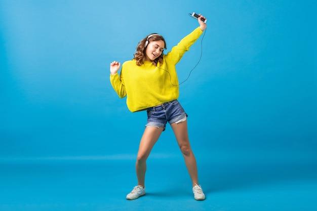 Attraktive lächelnde glückliche frau tanzt, die musik in kopfhörern im hipster-outfit lokalisiert auf blauem studiohintergrund hört, der shorts und gelben pullover trägt