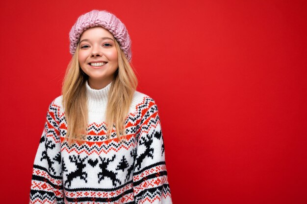Attraktive lächelnde glückliche junge blonde frau, die isoliert über buntem hintergrundwand trägt