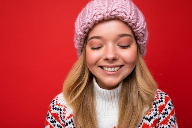 Attraktive lächelnde glückliche junge blonde frau, die isoliert über bunter hintergrundwand steht und das alltägliche stilvolle outfit trägt, das gesichtsgefühle zeigt.