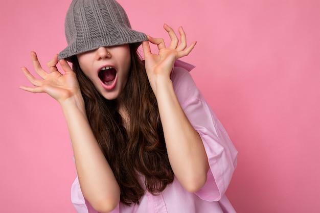 Attraktive lächelnde, glückliche junge brünette frau, die isoliert über einer bunten hintergrundwand steht und ein alltägliches, stilvolles outfit trägt, das gesichtsgefühle zeigt