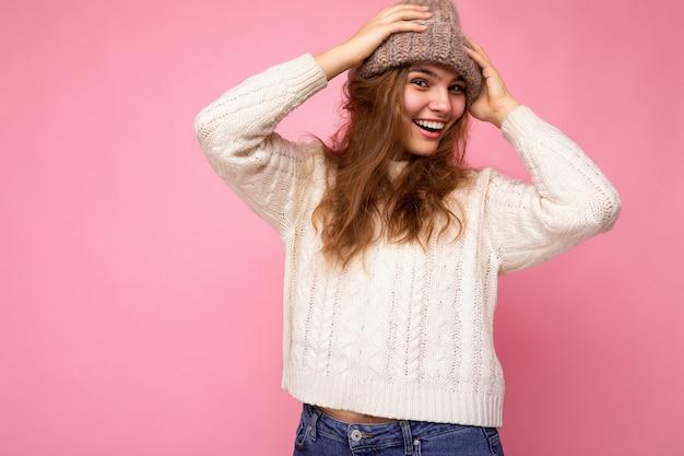 Attraktive lächelnde glückliche junge brunettefrau, die lokalisiert über buntem hintergrundwandtragen steht