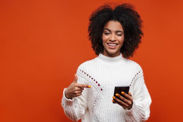 Attraktive lächelnde junge afrikanerin mit pullover, die handy isoliert über roter wand hält und mit dem finger zeigt