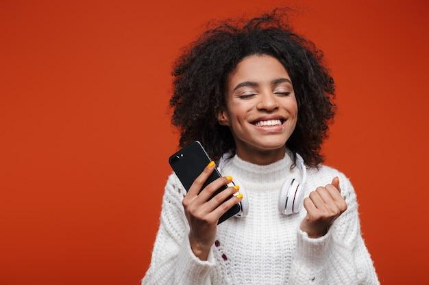 Attraktive lächelnde junge afrikanische frau mit pullover, die handy isoliert über roter wand hält und feiert