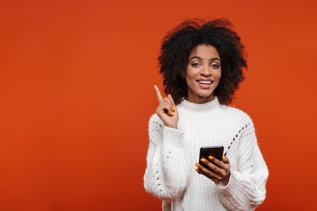 Attraktive lächelnde junge afrikanische frau mit pullover, die handy isoliert über roter wand hält und mit dem finger weg zeigt Premium Fotos