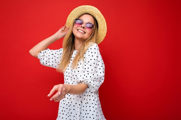 Attraktive lächelnde junge blonde frau, die alltägliche stilvolle kleidung und moderne sonnenbrillen trägt, die auf einer bunten hintergrundwand mit blick in die kamera isoliert sind