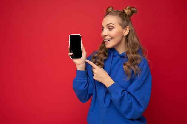 Attraktive lächelnde junge blonde frau, die einen stylischen blauen hoodie trägt, isoliert auf rotem hintergrund mit kopienraum, der das smartphone hält und das telefon in der hand zeigt, mit leerem bildschirm, der auf gadjet-look zeigt