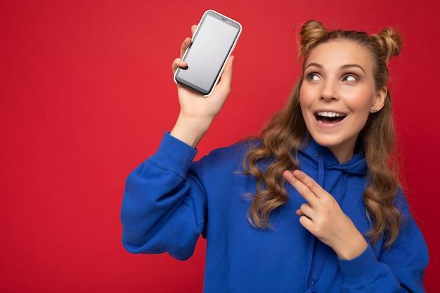 Attraktive lächelnde junge blonde frau, die stilvollen blauen kapuzenpulli lokalisiert auf rotem hintergrund mit trägt
