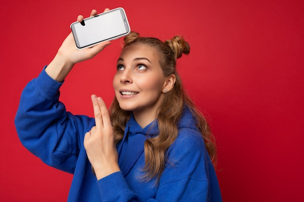 Attraktive lächelnde junge blonde frau trägt einen stilvollen blauen hoodie auf rotem hintergrund mit