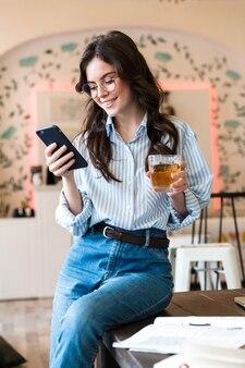 Attraktive lächelnde junge brünette frau, die im café drinnen studiert, handy benutzt, glas mit saft hält