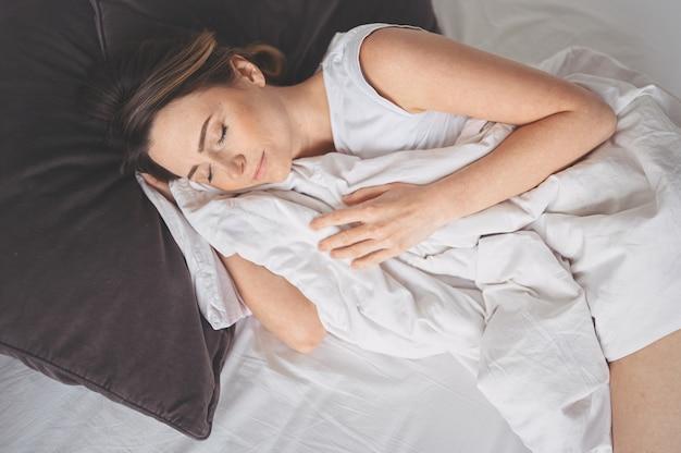 Attraktive lächelnde junge frau, die sich im bett ausdehnt und alleine aufwacht glückliches konzept, wach nach gesundem schlaf in gemütlichem bequemem bett und matratze genießen guten morgen