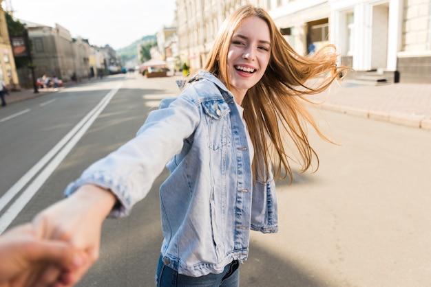 Attraktive lächelnde junge frau, welche die hand ihres freundes auf straße führt