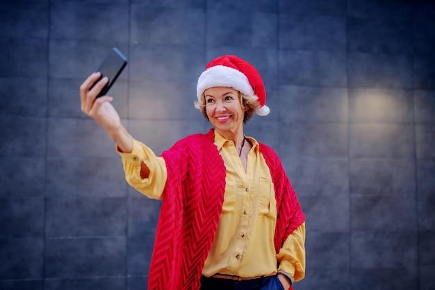 Attraktive lächelnde kaukasische ältere blonde frau mit weihnachtsmütze auf kopf, die aufwirft und selfie nimmt, während sie vor wand im freien steht.