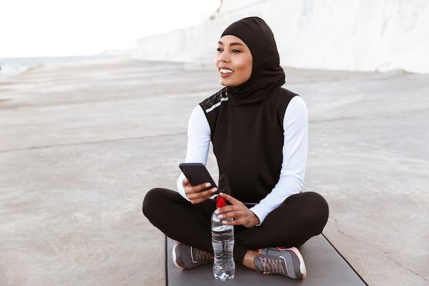 Attraktive lächelnde muslimische sportlerin, die im freien hijab trägt, auf einer fitnessmatte mit wasserflasche sitzt und handy benutzt