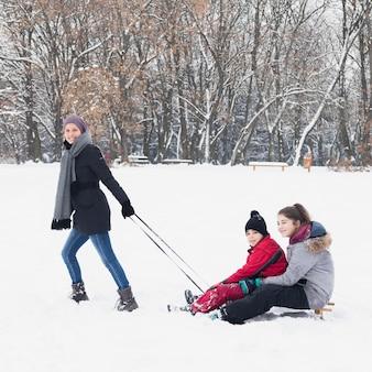 Attraktive lächelnde mutter, die ihre kinder auf schlitten im winter zieht