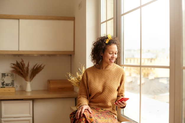 Attraktive lässig gekleidete junge lateinamerikanische frau, die auf der fensterbank in der küche sitzt, handy hält, das nachrichtenfeed über soziales netzwerk prüft oder textnachricht tippt, ruhe hat. technologie und kommunikation