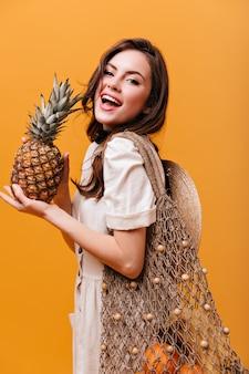 Attraktive langhaarige frau im weißen kleid posiert mit gestrickter einkaufstasche und hält ananas.
