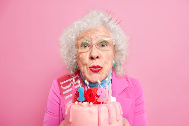 Attraktive lockige ältere europäische frau bläst kerzen auf kuchen feiert geburtstag macht wunsch feiern hat helles make-up trägt transparente brille