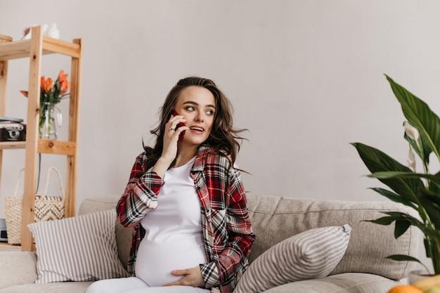 Attraktive lockige brünette schwangere frau, die auf handy spricht