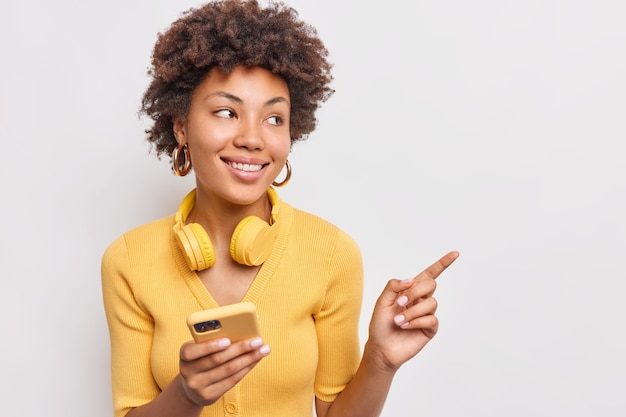 Attraktive, lockige junge frau mit sanftem lächeln hält moderne handy-kopfhörer um den hals, zeigt weg auf kopienraum, gekleidet in einem lässigen gelben pullover, isoliert über weißer wand