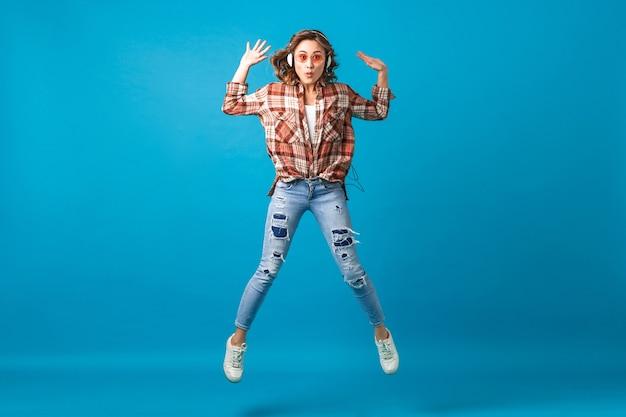 Attraktive lustige frau, die mit verrücktem gesichtsausdruck springt, der musik in den kopfhörern im karierten hemd und in den jeans lokalisiert auf blauem studiohintergrund hört