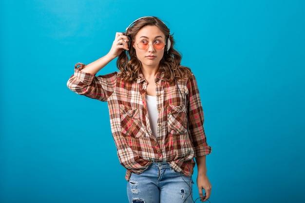 Attraktive lustige frau mit überraschtem verdächtigem gesichtsausdruck, der beiseite schaut, musik in kopfhörern in kariertem hemd und in jeans lokalisiert auf blauem studiohintergrund hört