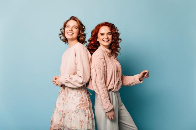 Attraktive mädchen, die mit lächeln auf blauem hintergrund aufwerfen. studioaufnahme von freundinnen, die positive emotionen ausdrücken.